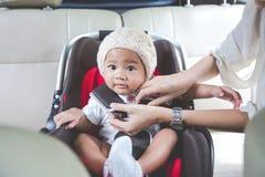 Bemuttern Sie das Sichern ihres Babys im Autositz in ihrem Auto Lizenzfreie Stockfotos