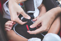 Bemuttern Sie das Sichern ihres Babys im Autositz in ihrem Auto Stockbild