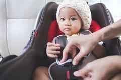 Bemuttern Sie das Sichern ihres Babys im Autositz in ihrem Auto Stockfotos