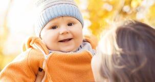 Bemuttern Sie das Spielen im Park mit ihrem Kleinkindbaby Mutter und Sohn über Saisonherbsthintergrund Lizenzfreie Stockfotografie