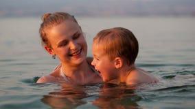 Bemuttern Sie das Spielen mit ihrem jungen Sohn im Strand stock video