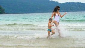 Bemuttern Sie das Spielen mit ihrem kleinen Sohn und Betrieb hinunter das Meer am tropischen Strand stock video footage