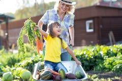 Bemuttern Sie das Spielen mit Kind im Garten im Dorf stockfotografie