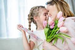 Bemuttern Sie das Umarmen der Tochter mit Postkarte an Mutter ` s Tag lizenzfreies stockfoto