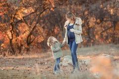 Bemuttern Sie das Umarmen ihres Kindes w?hrend des Wegs im Park stockfotografie