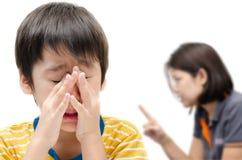 Bemuttern Sie das Unterrichten ihres schreienden Sohns auf weißem Hintergrund Lizenzfreies Stockbild