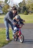 Bemuttern Sie das Unterrichten ihres Sohns, ein Fahrrad zu reiten Stockfoto