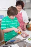 Bemuttern Sie das Unterrichten ihres Sohns, Fleisch zu kochen - Fett und Übergewicht stockfotografie