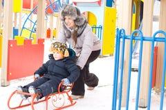 Bemuttern Sie den Druck ihres Sohns auf einem Winterschlitten Stockfoto