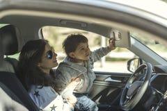 Bemuttern Sie die Aufwartung in Auto mit seinem kleinen Baby Stockfotos