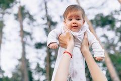 Bemuttern Sie die Hände, die herauf das frohe Baby der hohen Luft werfen Draußen gesunde Kindertätigkeit, aktiver Lebensstil und  Stockbild