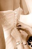 Bemuttern Sie die Justage des Hochzeitskleides auf eine Braut stockfoto