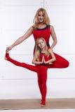 Bemuttern Sie die Tochter, die Yogaübung, Eignung, die Turnhalle tut, welche die gleichen bequemen Trainingsanzüge, Familiensport Stockbilder
