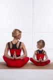 Bemuttern Sie die Tochter, die Yogaübung, Eignung, die Turnhalle tut, welche die gleichen bequemen Trainingsanzüge, Familiensport Stockfotografie