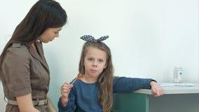 Bemuttern Sie die Unterhaltung mit ihrem kleinen Mädchen, das einen Lutscher in Doktor ` s Büro isst stock footage