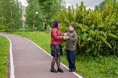 Bemuttern Sie die Unterhaltung mit ihrem Sohn im Park das Problem des Wachsens von Jugendlichen stockfotografie