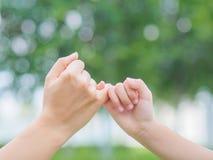Bemuttern Sie eine Hand ihres Kindertages im Frühjahr halten Lizenzfreie Stockbilder