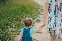 Bemuttern Sie eine Hand ihres Tages der Tochter im Frühjahr halten draußen Lizenzfreies Stockfoto