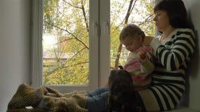 Bemuttern Sie Einfassungstochter ` s Haar auf dem Fensterbrett an einem bewölkten Herbsttag stock video footage