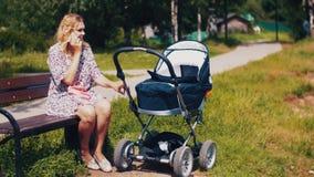 Bemuttern Sie Einflusskinderwagen und das Sprechen am Telefon auf Bank im Sommerpark sonnig stock footage