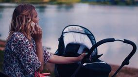 Bemuttern Sie Einflusskinderwagen und das Sprechen am Telefon im Sommerpark am See sonnig stock footage