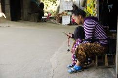 Bemuttern Sie ethnisches Hmong-Parentingkind und Spielenmobile am Haus stockbilder