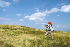 Bemuttern Sie Griffbabysohn an zurück im tragenden Rucksack, der in Berggebiete geht Lizenzfreie Stockfotografie