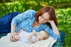 Bemuttern Sie Haben des Picknicks mit ihren entzückenden 2 Monate alten Baby Lizenzfreie Stockbilder