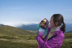 Bemuttern Sie halten ihren Sohn in der Hand mit Gebirgshintergrund Stockfotografie