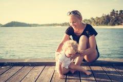 Bemuttern Sie helfen ihrem Kinderbaby, Strandseepier-Sommerferien aufzustehen stockfotos