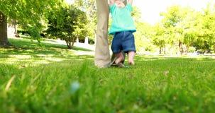 Bemuttern Sie helfenden Babysohn, um auf das Gras zu gehen stock video
