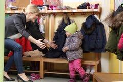 Bemuttern Sie ihr Kind von einem Kindergarten in der Garderobe aufheben lizenzfreie stockfotos