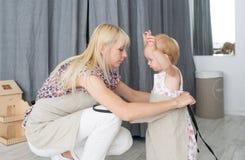 Bemuttern Sie ihre Tochter für die Hilfe bei einem Haushalt morgens kleiden Lizenzfreie Stockfotografie