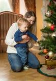 Bemuttern Sie, ihren Babysohn zeigend, wie man Weihnachtsbaum mit verziert stockbild