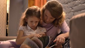Bemuttern Sie Lesebuch zur kleinen netten Tochter und Sitzen zusammen am modernen Wohnzimmer, Familienkonzept, zuhause stock video footage