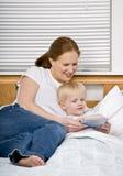 Bemuttern Sie Lesesohn eine Schlafenszeitgeschichte im Bett Stockbild