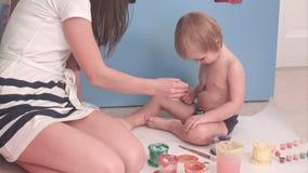 Bemuttern Sie Malerei auf ihrem Karosseriebau des kleinen Jungen er kitzlig stock footage