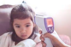 Bemuttern Sie messende Temperatur ihr krankes asiatisches kleines Kindermädchen stockbilder