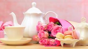 Bemuttern Sie ` s Tagesteeeinstellung mit Teekanne, macaron Plätzchen, rosa Rosen und Geschenk stockfoto