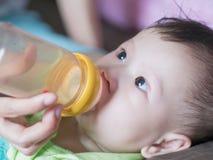 Bemuttern Sie Saugflasche ihr Baby, wachsame Augen des Babys noch Lizenzfreie Stockfotografie