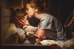 Bemuttern Sie setzt ihre Tochter, um zu Bett zu gehen und küsst sie am Abend lizenzfreie stockbilder