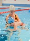 Bemuttern Sie Sohn eine Schwimmenlektion im Pool zuhause geben stockfoto