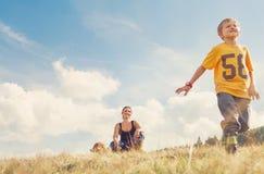 Bemuttern Sie Sohn und Hund auf dem goldenen Feld Lizenzfreies Stockfoto