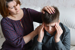 Bemuttern Sie Sorgfalt für ihren Sohn, der Kopfschmerzen hat stockfotos