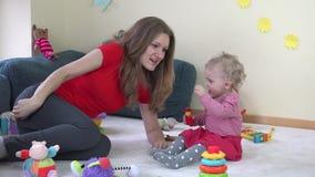 Bemuttern Sie Spiel mit kleiner Babytochter im Raum mutterschaft 4K stock video footage