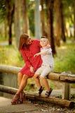 Bemuttern Sie Spiele mit ihrem kleinen Sohn auf der Bank lizenzfreie stockbilder