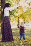Bemuttern Sie Spiele mit ihrem Sohn im Park im Herbst stockfotografie