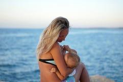 Bemuttern Sie stillend Baby auf dem Strand bei Sonnenuntergang nahe dem Meer Positive menschliche Gefühle, Gefühle, Freude Lustig Stockfotos