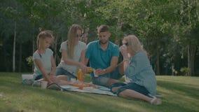 Bemuttern Sie strömenden Orangensaft in Gläser auf Picknick stock video footage