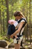 Bemuttern Sie tragende Tochter im Riemen in einem Wald lizenzfreies stockfoto